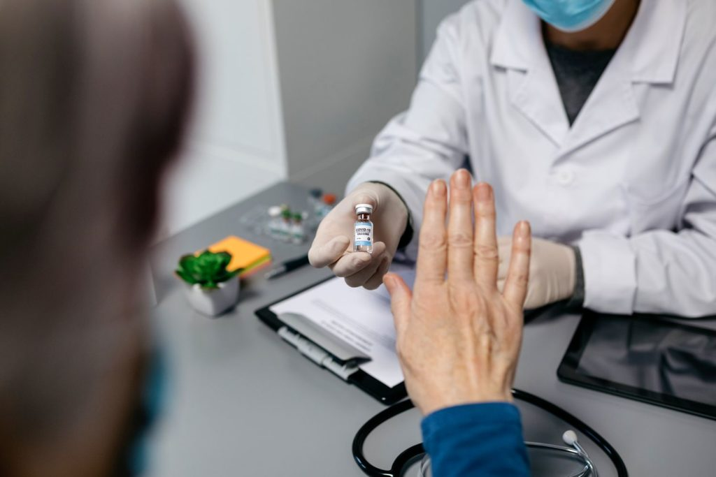Female patient refusing the coronavirus vaccine offered by her doctor